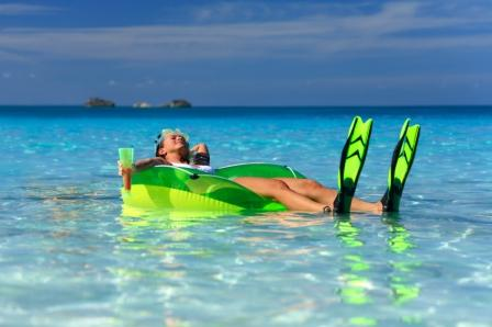 woman relaxing holding a beverage on a raft with snorkel gear